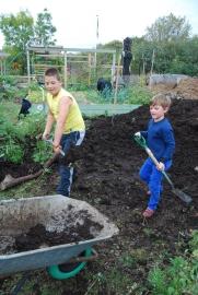 Nickolas and Sofian fill another wheelbarrow with manure